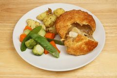Chicken pie and vegetables. Chicken pie with roast potatoes, Brussel sprouts, carrots and mange tout on a plate on a wooden tabletop stock photo