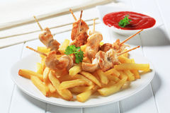 Chicken pieces on sticks and French fries Stock Image