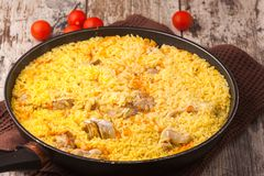 Chicken pilaf in a frying pan on wood table. With cherry tomatoes Stock Images