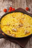 Chicken pilaf in a frying pan on wood table. With cherry tomatoes Royalty Free Stock Photography