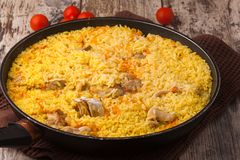 Chicken pilaf in a frying pan on wood table. With cherry tomatoes Stock Photos