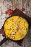 Chicken pilaf in a frying pan on wood table. With cherry tomatoes Royalty Free Stock Images