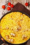 Chicken pilaf in a frying pan on wood table. With cherry tomatoes Stock Photo
