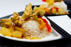 Chicken with pineapple and garnished with rice. On white and black plates Stock Images