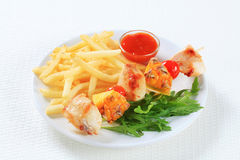 Chicken and pineapple skewer with fries Stock Images