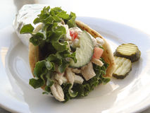 Chicken pita Greek style gyro sandwich. Served in silver foil on plate Royalty Free Stock Photo