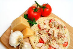 Chicken Pizza. Ready to cook, Grilled chicken, fresh tomatoes, garlic and grated Asiago cheese top this gourmet pizza for one topped off with dried herbs and Royalty Free Stock Photo
