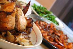 Chicken On A Platter. A plate of roasted chicken spread on the dinner table with prawns and vegetables in the background royalty free stock photos