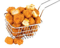 Chicken Popcorn In A Small Wire Frying Basket. Fried breadcrumb covered chicken popcorn in a small wire frying basket isolated on a white background stock photo
