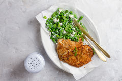 Chicken or pork schnitzel with cheese and peas salad royalty free stock image