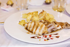 Chicken and pork  steaks garnished with potatoes in a white plate Stock Images