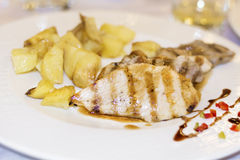 Chicken and pork  steaks garnished with potatoes in a white plate Stock Image