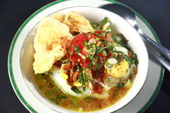 Chicken Porridge. Indonesian chicken porridge or bubur ayam, served in white bowl with chicken stock, boiled egg, slice of tomato and emping chips Stock Photo