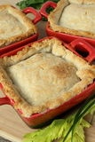 Chicken pot pies in a little melting pots. On a wooden board Royalty Free Stock Photography
