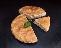 Chicken and potato pie with a segment cut out against black marble background. Closeup of a chicken and potato pie with a segment cut out against black marble Stock Images