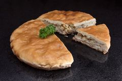 Chicken and potato pie with a segment cut out against black marble background Royalty Free Stock Photo