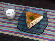 Chicken and potato pie segment with glass of milkt against black marble background Stock Photo