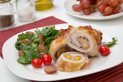 Chicken Prosciutto Roulade. Tasty chicken prosciutto roulade stuffed with cheese and pineapple, served with baby kale, grapes, and cherry tomatoes salad Royalty Free Stock Photo