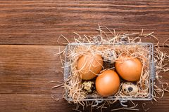 Chicken and quail eggs in a basket with straw. Top View Stock Photo