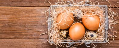 Chicken and quail eggs in a basket with straw. Top View Stock Image
