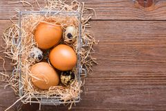 Chicken and quail eggs in a basket with straw. Top View Stock Images