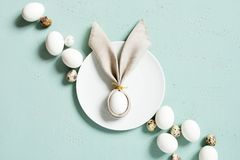 Chicken and quail eggs with bunny ears of linen napkin stock photo