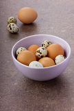 Chicken and quail eggs by Easter in the lilac ceramic bowl. On a brown surface Stock Photo