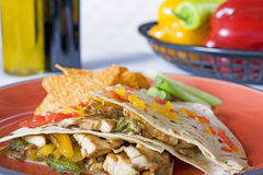 Chicken quasedillas on a plate. Chicken quasedillas with nachos and condiments and vegetables in the background Royalty Free Stock Photography