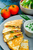 Chicken quesadilla. With tomato, red onions, parsley and red pepper, fresh salad and creame sour-chive dip Stock Photo