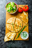Chicken quesadilla. With tomato, red onions, parsley and red pepper, fresh salad and creame sour-chive dip Royalty Free Stock Image