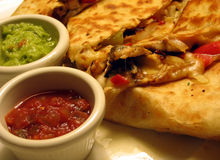 Chicken Quesadillas. This is a close up image of grilled chicken quesadillas with guacamole and salsa royalty free stock images