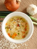 Chicken and rice soup. A bowl of chicken, vegetable and rice soup with onions, rice and garlic on the outside Stock Photo