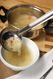 Chicken and rice soup. Being poured into a bowl from the pot with a ladle Stock Image