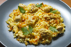 Chicken risotto with curry. On a blue plate Stock Photos