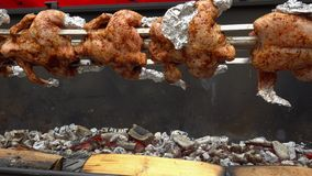 Chicken roasted on spit being grilled over the bright glowing coals stock footage