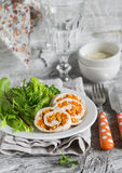 Chicken roulade with pumpkin and fresh green leaf lettuce on a white plate. On a light wooden background Stock Photos