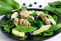Chicken salad with avocado, spinach and blueberries in black plate Stock Photo