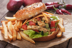 Chicken salad burger. With fresh vegetables and french fries Stock Photos