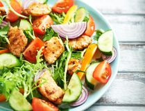 Chicken salad with cherry tomatoes, cucumber, endive, yellow and orange pepper and red onion. Concept for healthy eating and nutri Stock Photography