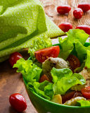 Chicken salad with cherry tomatoes and lettuce. On wooden background Stock Photo