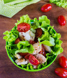 Chicken salad with cherry tomatoes and lettuce. On wooden background Royalty Free Stock Photography