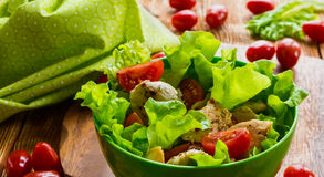 Chicken salad with cherry tomatoes and lettuce. On wooden background Stock Photos