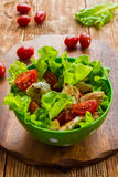 Chicken salad with cherry tomatoes and lettuce. On wooden background Stock Image