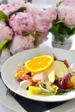 Chicken salad with fruits and flowers stock image