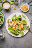 Chicken salad with green mix salad leaves served in plate on gray stone table, top view. Stock Photo