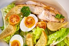 Chicken salad with leaf vegetables, chard, eggs, bulgur and cherry tomatoes. Stock Photo