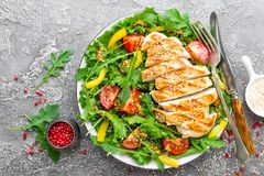 Chicken salad. Meat salad with fresh tomato, sweet pepper, arugula and grilled chicken breast. Chicken fillet with fresh vegetable. Salad on plate Royalty Free Stock Images