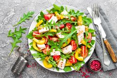 Chicken salad. Meat salad with fresh tomato, sweet pepper, arugula and grilled chicken breast. Chicken fillet with fresh vegetable. Salad on plate royalty free stock photo