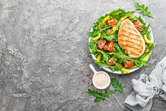 Chicken salad. Meat salad with fresh tomato, sweet pepper, arugula and grilled chicken breast. Chicken fillet with fresh vegetable stock image