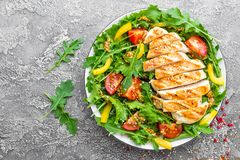 Chicken salad. Meat salad with fresh tomato, sweet pepper, arugula and grilled chicken breast. Chicken fillet with fresh vegetable Royalty Free Stock Image